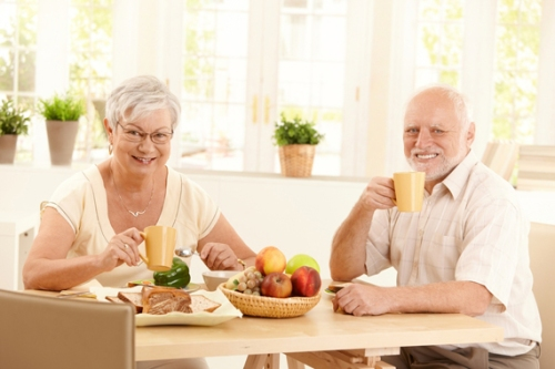 Senior couple having tea at breakfast, sitting in sunny kitchen, smiling.
